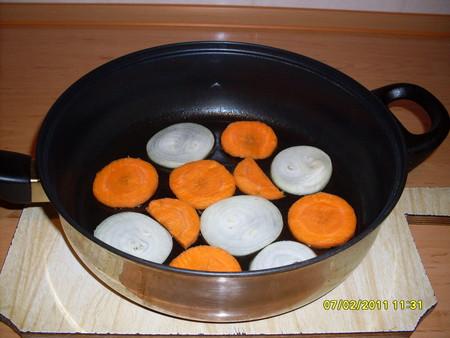 В сковороду налейте немного масла и разложите лук и морковь