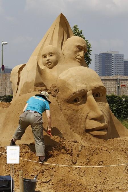 Скульптор работает над своим произведением из песка