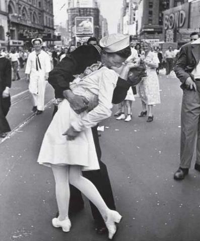 Автор: Альфред Эйзенштадт<br /> «Безоговорочная капитуляция»<br /> Автор прогуливался по площади и снимал целующихся. Затем он заметил моряка, который «бегал по площади, обнимал и целовал всех женщин подряд без разбору: тонких и толстых, старых и молодых. Я наблюдал, но определенного желания сделать фотоснимок не появлялось. Но вдруг матрос обнял нечто белое. Я успел поднять фотокамеру и снять его, целовавшего медсестру».<br /> Для тысяч американцев данная фотография, названная Эйзенштадтом «Безоговорочная капитуляция», стала символом завершения второй мировой войны.