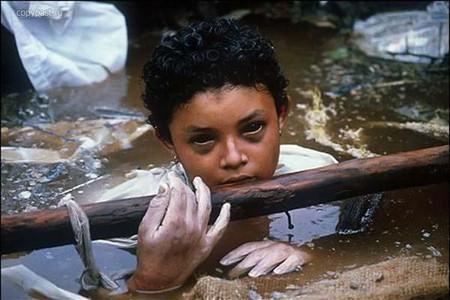 На фото отображена страшная трагедия — 13.11.1985 года- извержение колумбийского вулкана Невадо дель Руис. Мутная каша из потоков земли и грязи поглощала собой все живое. Погибло больше 23-х тысяч человек. В кадр за несколько часов до гибели попала девочка — Омаира Санчез, которая не смогла выбраться из грязевой жижи, поскольку ноги ее были сдавлены огромной бетонной плитой. Спасатели пытались сделать всё, что было в их силах. Девочка держалась очень мужественно и подбадривала всех окружающих. В страшной западне, надеясь на спасение, она провела три долгих дня. На четвертый день у нее начались галлюцинации и от подхваченных вирусов она скончалась.