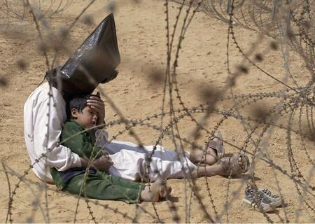 Автор: Жан- Марк Бужу, Франция<br /> 31.03.2003 года. Ирак, Ан Нажав.<br /> Отец заботится о сыне в лагере для военнопленных