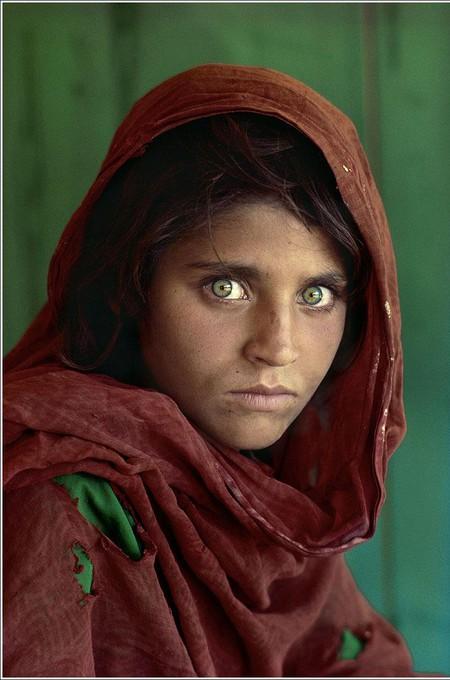 """Автор: Стивен Маккьюри<br /> """"Двенадцатилетняя афганская девочка""""<br /> Эта знаменитая фотография, сделана автором в одном из лагерей для беженцев, расположенном на границе Пакистана и Афганистана. Вертолеты СССР разрушили родную деревню юной беженки, а вся семья ее погибла, и, перед тем, как попасть в лагерь для беженцев, девочка проделала через горы двухнедельный путь. Эта фотография становится иконой National Geographic после ее публикации в июне 1985 года. С этого момента образ девочки тиражируется повсеместно — от ковриков до татуировок, что сделало фотографию одной из наиболее растиражированных в мире."""