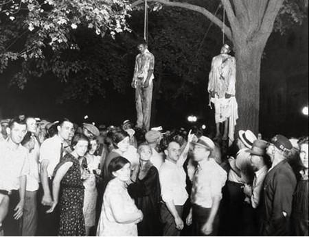 """Автор: Лоуренс Бетлер<br /> """"Суд Линча"""", 1930<br /> Этот снимок был сделан, когда толпа из десяти тысяч белокожих людей повесила двух чернокожих мужчин за то, что те изнасиловали белую женщину и убили её парня. Толпа «освободила» заключенных из тюрьмы, чтобы подвергнуть их линчеванию. Поразительным контрастом выступают радостные лица белых людей как фон для повешенных трупов."""